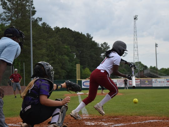 Pineville's Hailiee Wilkins (7, right) bunts against