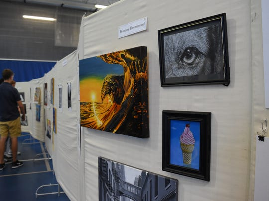 People pause to look over art pieces at a gallery exhibit inside the Naples High School gymnasium on April 25, 2017. This was the first AP art show exhibiting work done by students from three high schools in the district.
