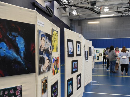 People discuss art at a gallery exhibit inside the Naples High School gymnasium on April 25, 2017. This was the first AP art show exhibiting work done by students from three high schools in the district.