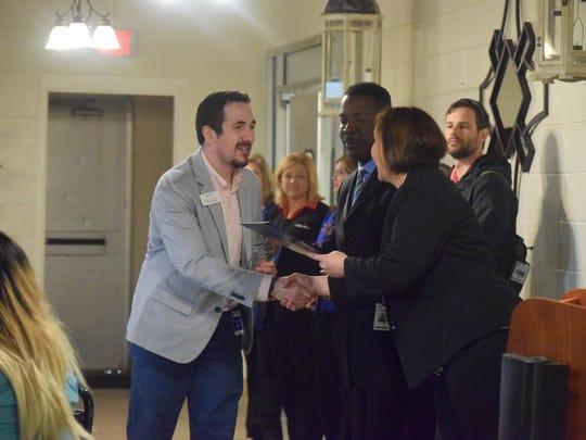Alex Caudill, of the Henderson Area Arts Alliance, accepts an award on the behalf of Senator Dorsey Ridley.