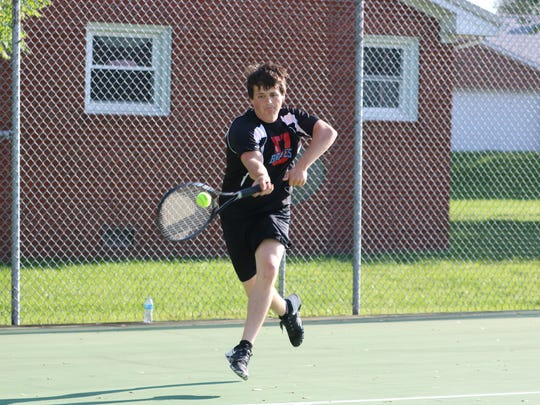 Tyler Steelman goes for a hit during a match against Henderson during doubles.