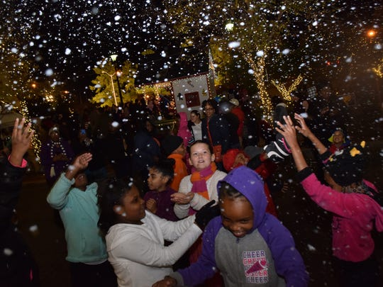 Children enjoy playing in the falling snow from a snow machine at Alex Winter Fête.