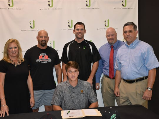 Catholic High senior Sam Carpenter (seated) is joined by his parents and workout coaches after he signed to continue education at Flagler University where he will be on academic scholarship and invited walkon to baseball team. He is joined left to right by his mother Melanie, his strength coach, Travis Mattair, owner of Unlimited Training Academy, Rusty Deason, his catching coach and his father Marc.