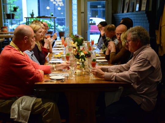 A group gathers for a Charleston themed chef dinner. Vito Palmietto hosts monthy dinners. The table they are eating at was made from wood salvaged from the 2007 ice storm. Palmietto said the storm brought people together and food brings people together.