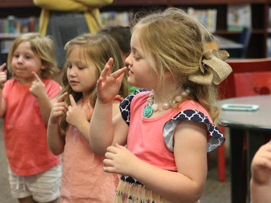 JP II Girls reach for their noses during a dance at the library. Left to right: Kate Dunn, Nya Beaven, and Allie Thomas.