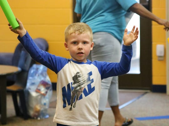 Reed Arnett waves his drum stick in the air as he dances along to the music at the library.