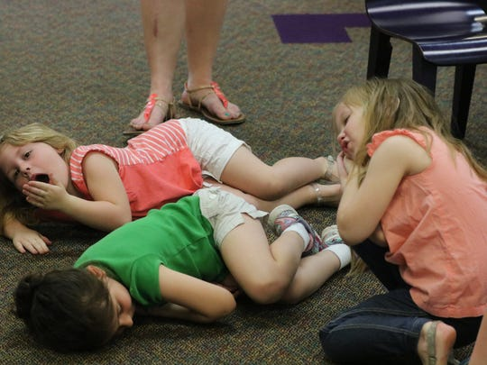 L to r: Kate Dunn, Ellie Thomas, and Nya Beaven pretend to sleep during their activities at the library.
