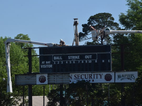 Crews work on the scoreboard at Bringhurst Field Tuesday. The outfield wall was taken down over the weekend.