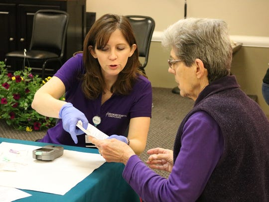 Kim Lamb of UC Methodist Hospital labs goes over a blood sample with Pat Rudd.