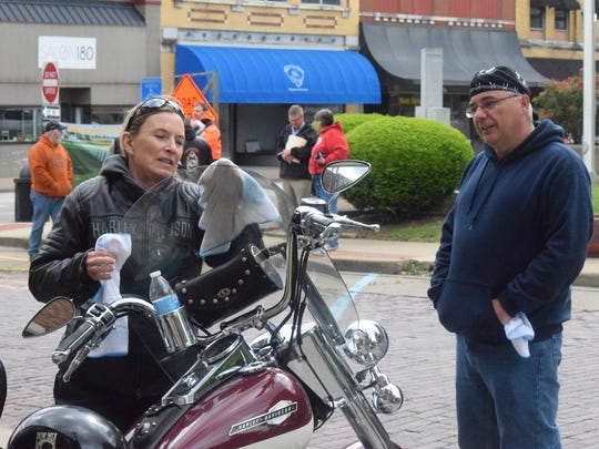 Brenda Williams wipes her motorcycle clean as Allen Olsen watches nearby.