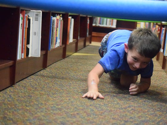 Brayden Howell, a kindergartner at Morganfield Elementary School, makes his way through the obstacle course set up in the public library last Tuesday.