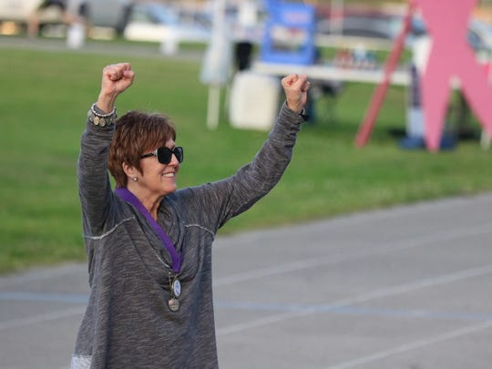 Rosemary Trowbridge lifts her hands in victory after completing her Survivor Lap around the track.
