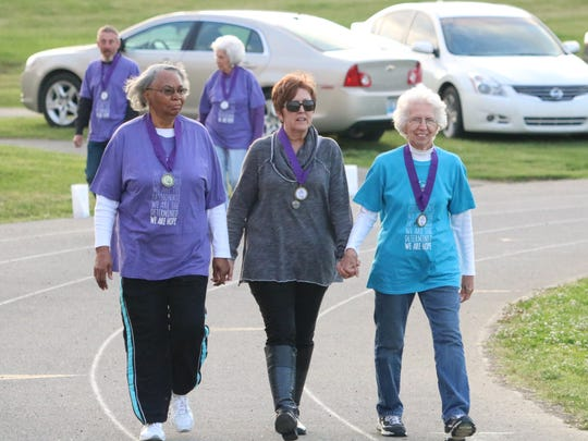 Sarah Wilson, Rosemary Trowbridge, and Gina Loxley lock hands as they complete the survivors lap around the track.