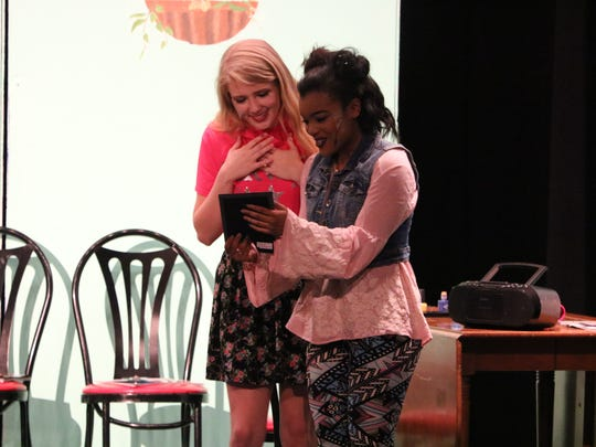 Caroline O'Guin as Elle Woods and JaQuazia Fletcher as Paulette smile at a photo in one of the scenes. O'Guin and Fletcher are both UCHS seniors this year.