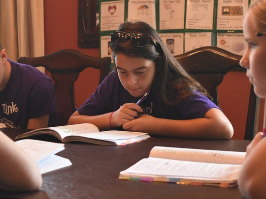 Kaitlyn Carlson, 12, looks intently at her notes from past practices with her Think Tank team inside her Estero home on May 5, 2017. The team is gearing up to compete in the Odyssey of the Mind World Finals in late May.