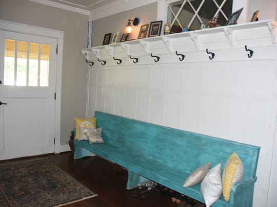 The entryway of the home features a painted bench and transom window (re-purposed from the front of the house) which offers a warm, inviting area to gather.