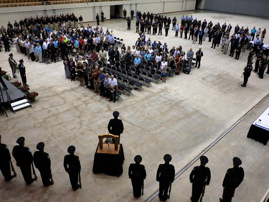 Attendees stand together as Taps plays during the Knoxville-Knox County Peace Officers Memorial Service at the Civic Coliseum in Knoxville, on Thursday, May 18, 2017.  (Shawn Millsaps/Special to News Sentinel)