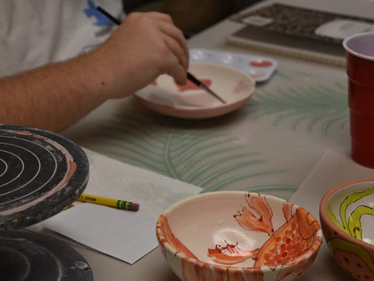 Aktion Club members paint empty bowls during the first