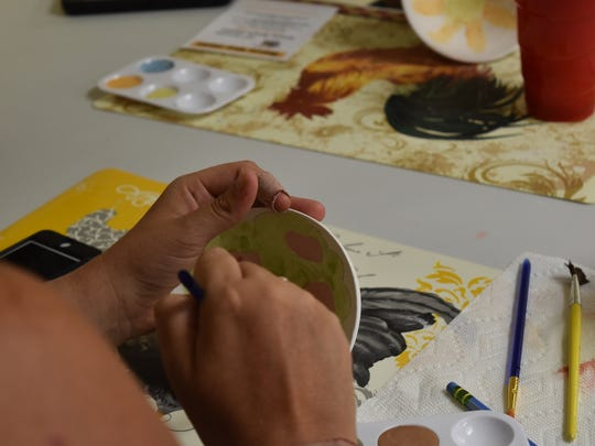An Aktion Club member shows off her bowl painting skills during the first Club event in Naples on May 18, 2017. The club helps adults living with disabilities engage with the community.