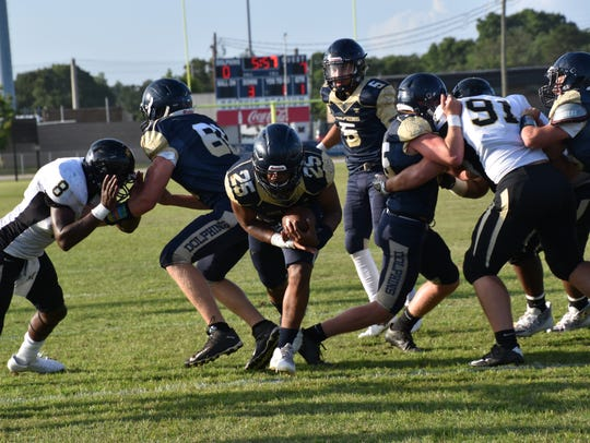 Gulf Breeze HIgh's Carl Taylor burst through big hole