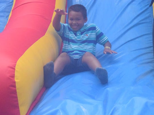Javant Williams is all smiles as he makes his way down the bouncy house slide.