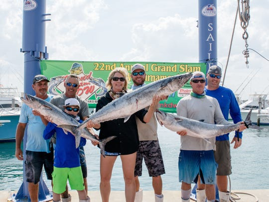 """Kari Townsend, pictured at center, was the winner of the """"heaviest overall"""" fish award by a female angler - for this 43.1 lb kingfish on the """"Sword A Broke"""" vessel."""