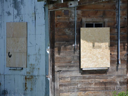 City workers added more boards to broken windows on the granary building to prevent people from going inside.