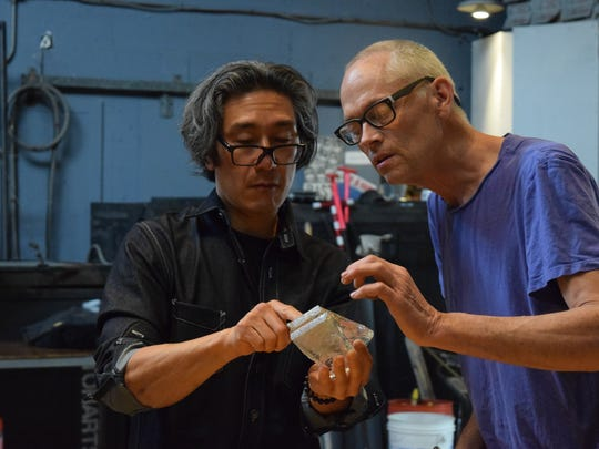 Artist Michael Joo was invited to participate in the Emanation 2017  residency and exhibition project at WheatonArts.  Here in the WheatonArts Glass Studio he reviews with Creative Director Hank Adams pieces of a glass palate for his installation.