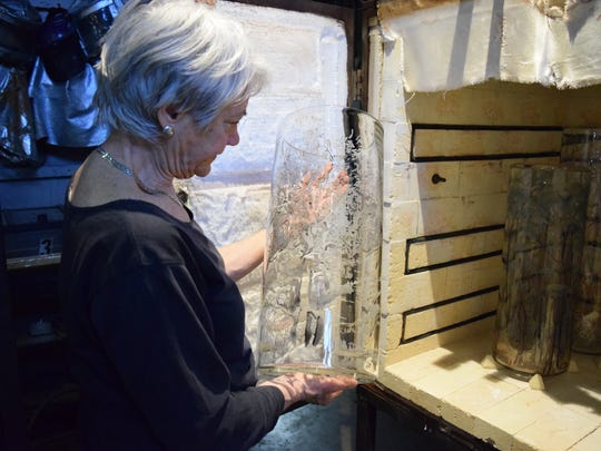 Longtime Philadelphia artist and painter Emily Brown   reviews a cylinder coming out of an annealing oven in the WheatonArts Glass Studio, which heats the piece to fuse the enamel paint to the glass.   She was invited to explore painting on glass as part of  the 'Emanation 2017' residency and exhibition project at WheatonArts.