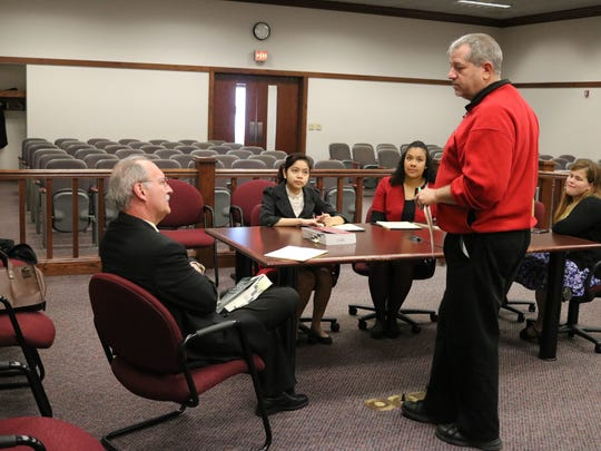 Greg Scalf, standing, social studies teacher at Port Clinton High School, discusses the mock trial case for Student Government Day with junior students and George Wilber, Port Clinton law director.