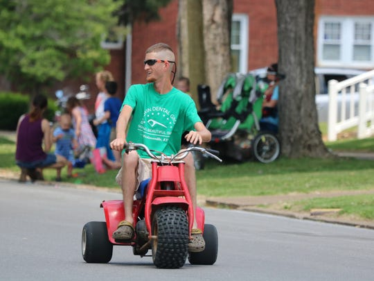 Tyler Alvey rides in the parade on his three-wheeler.