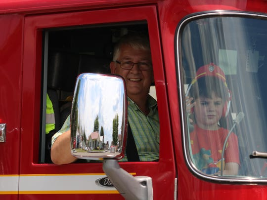 Sturgis Mayor Mike Hardesty and his grandson, Kaleb Chatham, ride along in one of the fire trucks during the parade.