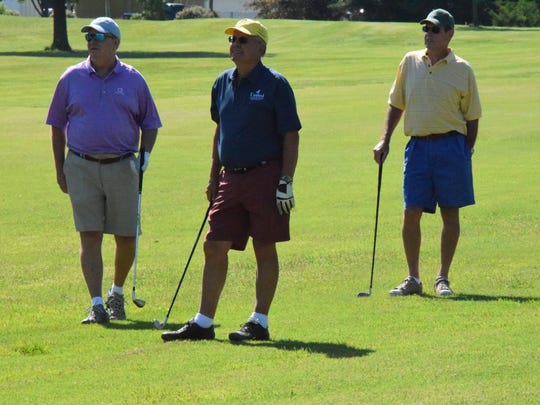 Steve Cox, Eddie Steward, and Kenny Holt watch to see where the golf ball will land.
