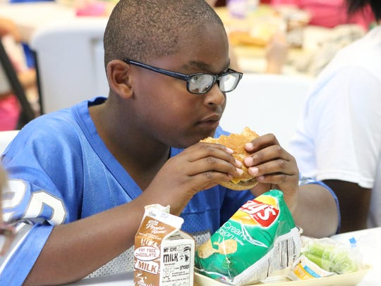 Deshawn McHenry eats his burger during the Summer Read