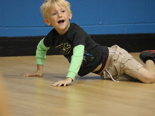 Lincoln Hunley plays a game on the floor during recreation time at VBS.