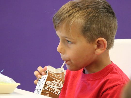 Brennan Boyd takes a sip of his chocolate milk during lunch at the Morganfield branch for Summer Read and Feed.