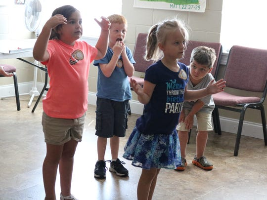 Lakyn Johnson, Nolan Phillips, Brelynn Ferrell, and Buck Logan participate in a dance activity during their VBS class.