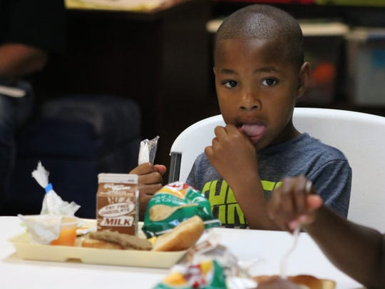 Prestyn Norris gets ready to eat his meal at Summer Read and Feed at the UC Public Library.