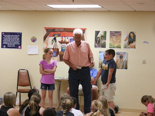 Mr. Ron Gish (center) leads Paige Steward and Zachary Powell in an activity during VBS.
