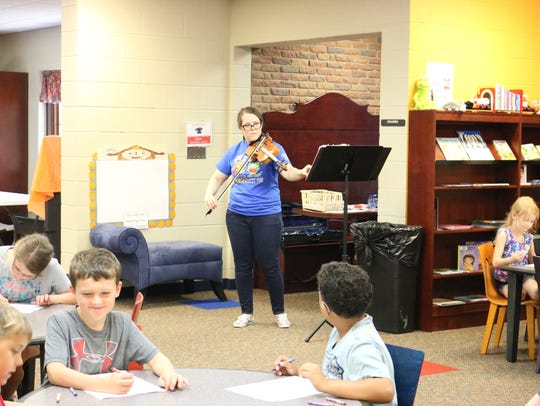 Christa Duke plays her violin during an activity for