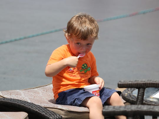Colton Payne enjoys a refreshing snow cone in the heat of day at the Morganfield Home Center.
