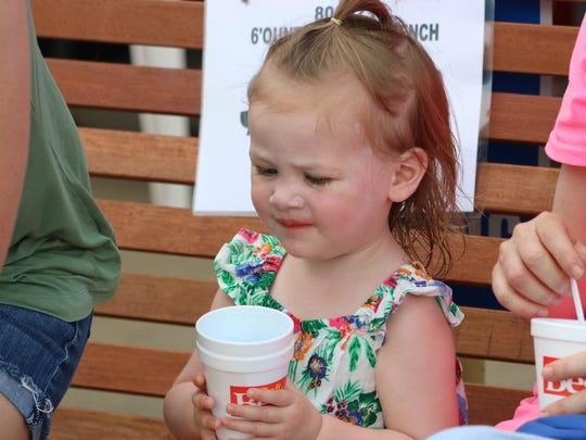 Lydia Rose Elder eats a snow cone to cool off during the Kids Day event at the Morganfield Home Center.