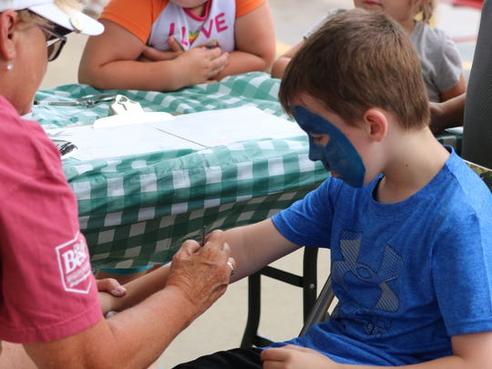 Case Septer gets his arm painted after a face painting at the Kids Day event.
