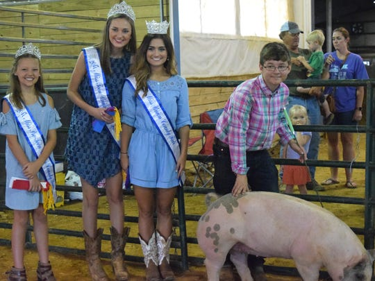 Kynlee Clark, Paige Wells, Tori French and Dillon Shaw pose for a picture with Shaw's grand champion hog.