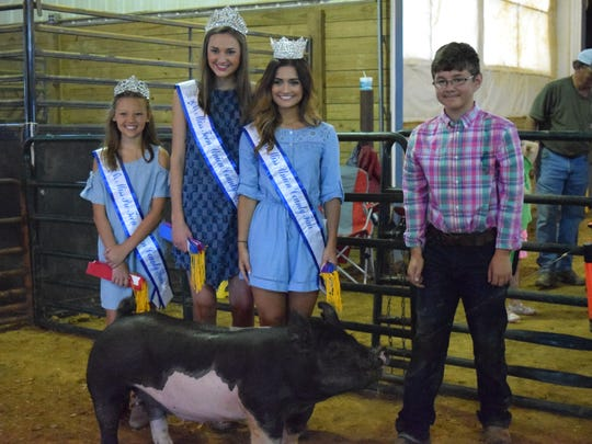 Kynlee Clark, Paige Wells, Tori French and Dillon Shaw smile with Shaw's hog, which one for showmanship.