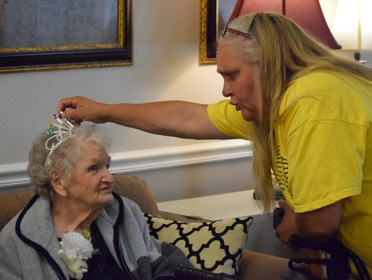Martha Russelburg gets her crown adjusted by one of