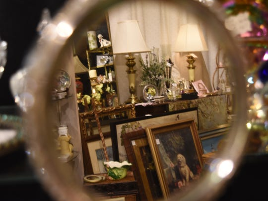 An antique mirror reflects just some of the thousands of items sold at Treasure Island Antiques off of U.S. 41 in Naples. More than 40 vendors offer items such as jewelry, furniture, vinyl records, clothes, and porcelain figurines.
