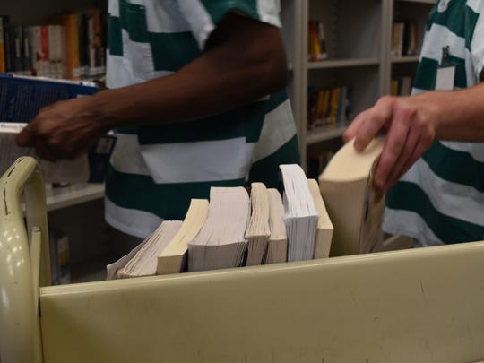 Inmate librarians organize books inside the library at the Naples Jail in the Collier County Government Complex. The Naples locale has offered a library to inmates since the 1980s, using donated books worn over the years. Recently, the locale was digitized with software used at Collier County libraries.
