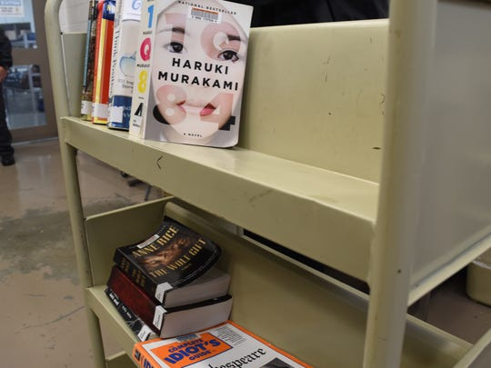 Inmate librarians organize books on the shelves inside