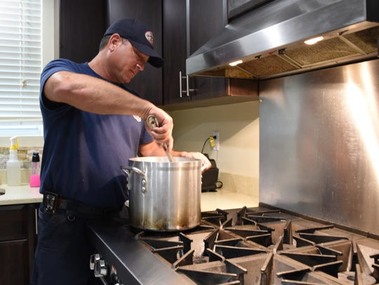 Capt. Craig Weinbaum stirs chili inside a pot at the